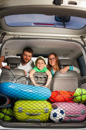 Happy family, young parents and kid boy, sitting on the car seat, view from the boot full of luggage