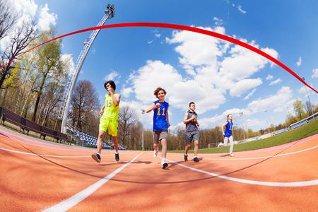 atletismo: Grupo de cuatro participantes jóvenes de maratón, los adolescentes varones y una niña que se ejecutan en la recta final, vista a través de la cinta roja