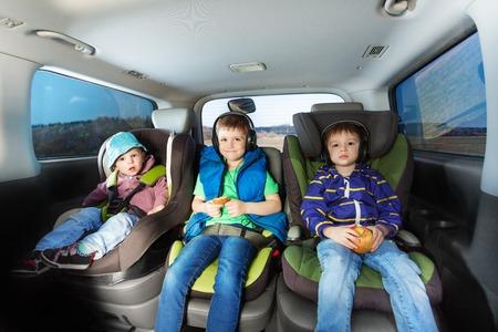 Trzy szczęśliwe chłopcy, wiek-różnorodna bracia siedzą w fotelikach samochodowych bezpieczeństwa, snaking i słuchania muzyki podczas podróży samochodem Zdjęcie Seryjne