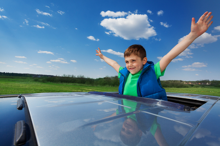 sunroof: Portrait of happy smiling five years old boy enjoying freedom on the sunroof of a car
