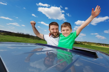 sunroof: Portrait of happy family, father with his five years old son, enjoying freedom on the sunroof of their car, against beautiful landscape
