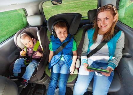Twee gelukkige jongens en moeder zijn gespeld met veiligheidsgordel in een auto, jongens die in de veiligheidsautostoel zitten