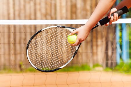 Close-up of female hand holding tennis ball and racket, player starting set outdoor in summer