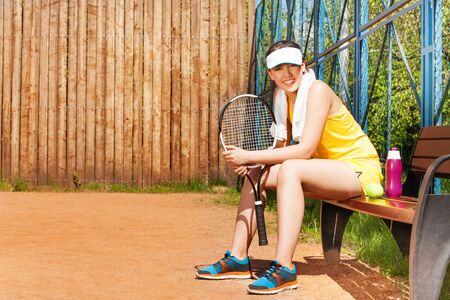 player bench: Happy teenage girl, tennis player, having rest after the game sitting on the bench on the clay court