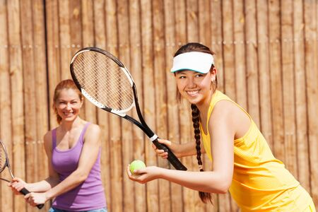 fun activity: Portrait of female double tennis partners starting set outside in summer Stock Photo