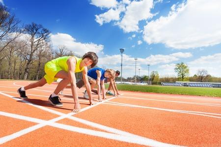 Vista laterale di tre atleti adolescenti, ragazzi in abiti sportivi in ??fila pronti a correre sullo stadio