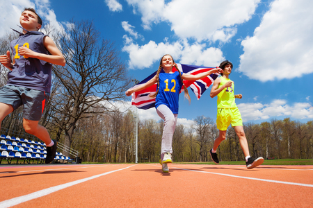 racetrack: Team of three teenage sprinters, boys and girl, running with British flag on the track