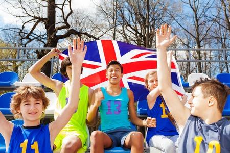 ropa deportiva: aficionados a los deportes adolescentes multiétnico feliz celebrando y apoyando su equipo, que se sientan en la tribuna y ondeando la bandera de Gran Bretaña