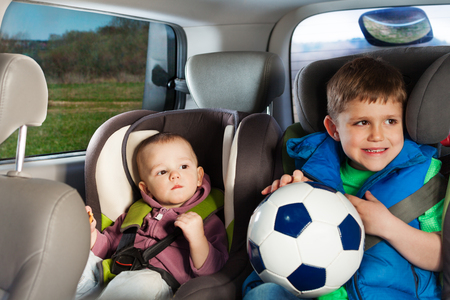 buckled: Two happy little travelers, age-diverse brothers, playing ball, sitting in a child safety seats