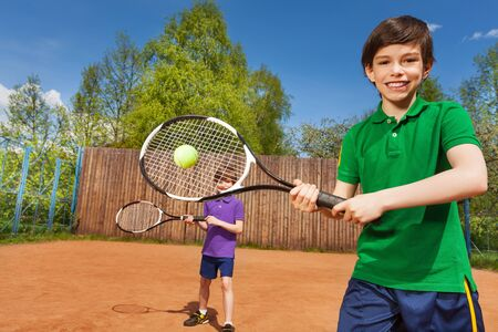 child sport: Portrait of happy tennis player, kid boy hitting forehand and his partner behind him on the tennis court Stock Photo