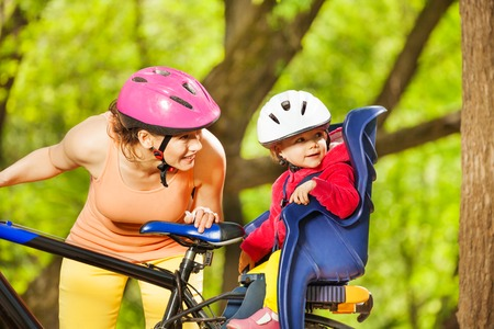 helmet seat: Happy mother and her little toddler daughter, sitting in bike seat with helmet, riding a bike together in the park