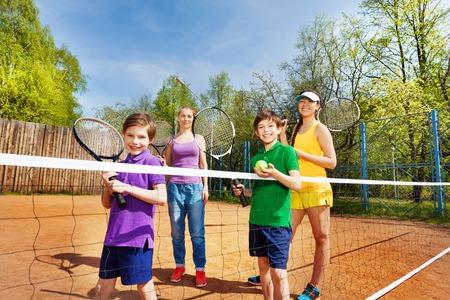 jugando tenis: Familia feliz, dos hermanos, su hermana y su madre, de pie, con raquetas de tenis y pelota en la cancha de arcilla en verano