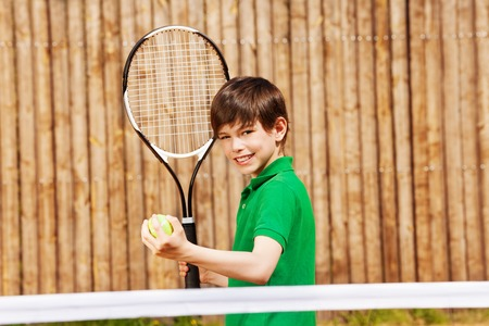 Happy young boy, tennis player, starting tennis set, holding racket and ball outside in summer Stock Photo