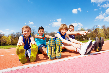 Portrait of four happy teenage kids sitting in a row doing stretching exercises outdoors on the stadium Stok Fotoğraf