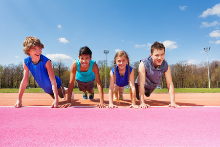 Four happy smiling teenagers doing push-up exercises standing in a row outdoor on the track