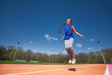 Tiener fitness meisje springt touw buiten in het stadion op zonnige dag