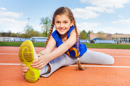 Happy smiling teenage girl in sportswear stretching legs outdoor in the stadium Stock Photo