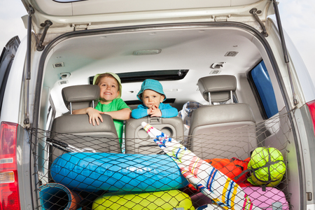 Two little travelers, age-diverse brothers, peeking from behind a car seat, view from the boot full of luggage