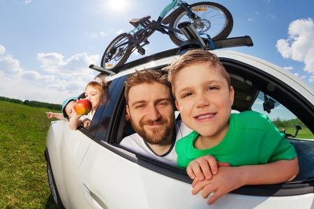 Big happy family, jonge vader en drie leeftijd diverse jongens, gaat op vakantie reis met de auto in de zomer