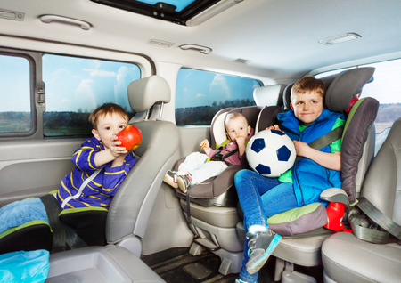 snacking: Three little boys, age-diverse brothers, travelling by car in safety seats, snacking and playing ball during the trip