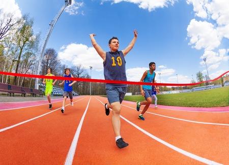 Portret van tiener sprinter, race kampioen, kruising finish lijn op het stadion