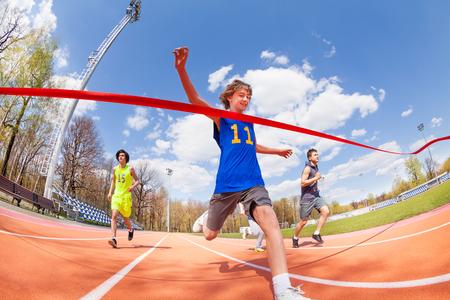 El velocista adolescente feliz de ganar la carrera y que viene primero en terminar la cinta roja sobre grupo de deportistas en la pista