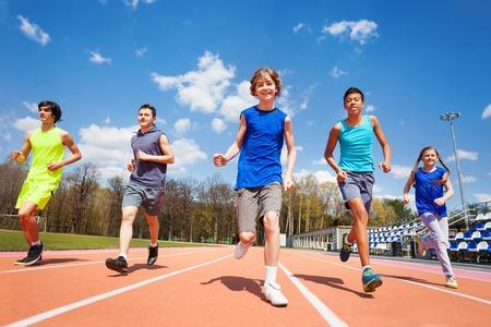 Groep van vijf gelukkige tieners in sportkleding, die draait op het stadion op een zonnige dag