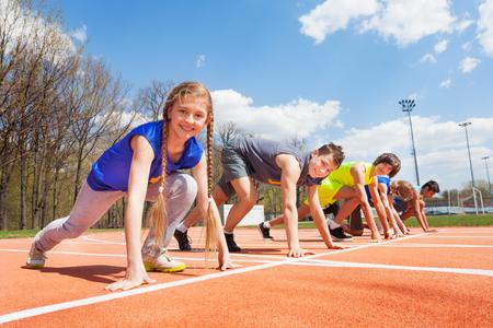 Seitenansicht von fünf Teenager-Sprinter in der Sportkleidung aufgereiht bereit im Stadion zu laufen Standard-Bild - 61223894