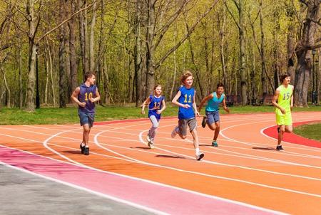 Vijf running tiener atleten, multi-etnische jongens en meisjes, buiten in het stadion