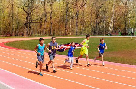 ropa deportiva: Grupo de cinco adolescentes velocistas multiétnicas correr con la bandera de Gran Bretaña en la pista Foto de archivo