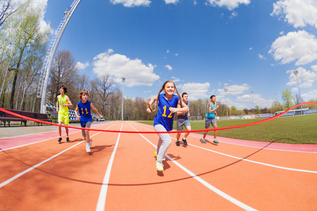 Portrait of five happy teenage sprinters running to the finish line on the stadium Archivio Fotografico