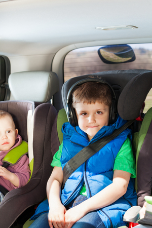 buckled: Portrait of five years old boy listening to music in the headphones, sitting in the child safety seats