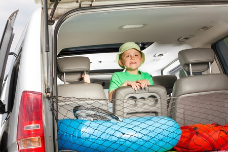 tripping: Happy five years old boy in green tee and bucket hat, standing on a car seat, view from the luggage boot