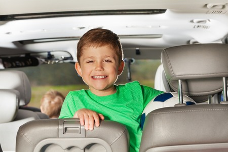 five years old: Close-up portrait of happy five years old boy sitting in the car and holding ball Stock Photo