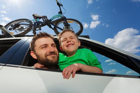 Ritratto di viaggiatori felice, padre e suo figlio bambino, guardando fuori dalla finestra di una macchina durante il viaggio estivo