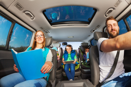 Happy parents traveling by car with three boys, and mother holding book or magazine, inside view Stock Photo