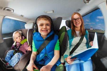Happy smiling family, mother and two age-diverse boys travelling by car, and mother reading book Stock Photo