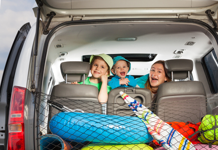 Cute young mother with her age-diverse sons peeking from behind a minivan seat, view from the boot full of luggage