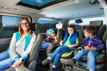 Portret van jonge moeder en drie leeftijdsdiverse jongens zitten in de veiligheid autostoelen Stockfoto