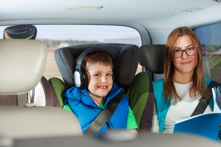 buckled: Portrait of happy car passengers, mother and her kid boy, sitting in the child safety seat, listening to music and reading book with copy-space