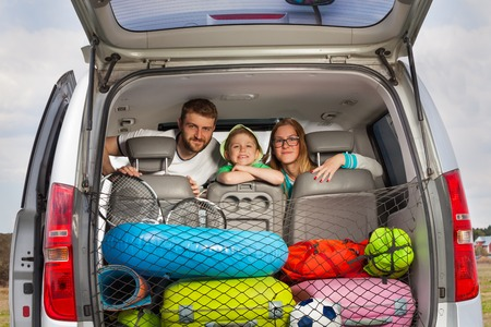 Happy young parents with their five years old son, sitting in their minivan, view from the car boot full of luggage