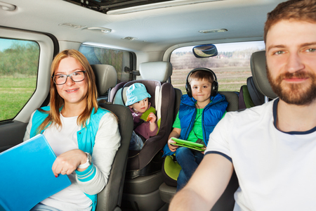 Close-up portrait of young parents travelling by car with two boys, sitting in the safety car seats