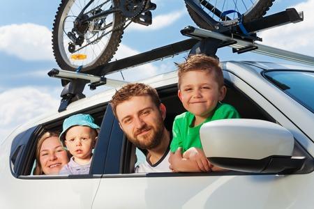 Gelukkige familie, ouders met twee leeftijdsdiverse zoons, kijkt uit het raam van de auto in de zomer reis