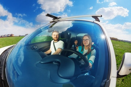 Female driver, beautiful young mother, driving a car with her family on the summer vacation, wide angle lens Stock Photo