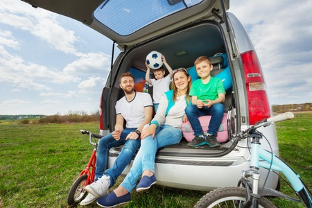 Happy family, young parents and two kid boys, sitting in the luggage boot, going for a car trip in summer Archivio Fotografico