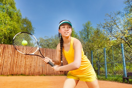 Portrait of teenage Asian girl, tennis player, servicing on the clay court in summer Stock Photo