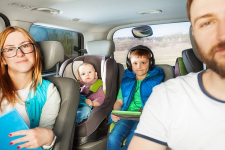 Happy young family, mother, father and two little boys having fun travelling by car