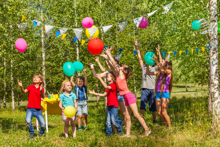 kids having fun: Big group of happy kids having fun playing balloons at the outside birthday party in summer