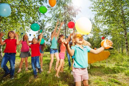 귀여운 소녀 여름 공원에서 그녀의 친구와 함께 다채로운 풍선을 연주
