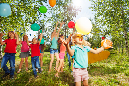 Cute little girl playing colorful balloons with her friends at summer park Standard-Bild